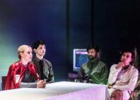 Kobieta siedząca za stołem w czerwonej pelerynie z białym krzyżem, dalej postacie trzech mężczyzn siedzących przy stole, dwóch ubranych w koszule z czarnym krawatem, jeden w samej koszuli. W tle telewizor oraz sztuczna palma