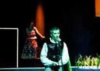 Na pierwszym planie mężczyzna stojący przy mikrofonie, za im drugi mężczyzna w damskiej spódnicy rozbierający gorset.