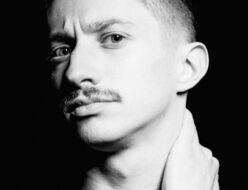 Czarno-biała fotografia. Mężczyzna z wąsem, ubrany na czarno patrzy w obiektyw. Jedną dłonią trzyma się za szyję. Ma zmarszczone czoło. Na fotografii: Konrad Cichoń.