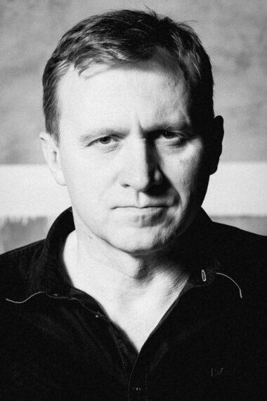 Czarno-biała fotografia. Mężczyzna patrzy prosto w obiektyw. Jest ubrany na czarno. Na zdjęciu: Piotr Kaźmierczak.