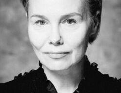 Czarno-biała fotografia. Kobieta ze związanymi włosami wpatruje się w obiektyw. Ma na sobie bluzkę z koronkową kołnierzem. Na zdjęciu: Ewa Szumska.
