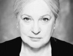 Czarno-biała fotografia. Kobieta o jasnych włosach wpatruje się w obiektyw. Ma na sobie białą bluzkę i czarną narzutę. Na zdjęciu: Teresa Kwiatkowska.