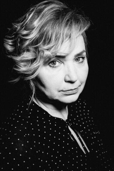 Czarno-biała fotografia. Kobieta z zebranymi długimi włosami patrzy się w obiektyw. Na zdjęciu: Barbara Krasińska.