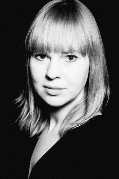 Czarno-biała fotografia. Kobieta o długich jasnych rozpuszczonych włosach wpatruje się w obiektyw. Ubrana jest na czarno. Na zdjęciu: Kornelia Trawkowska.
