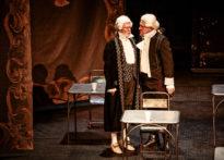 Dwóch aktorów na scenie pomiędzy stolikami, krzesłami i wiszącymi arrasami, ubrani w peruki i epokowe stroje