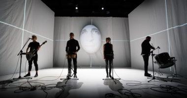 Cztery postacie ubrane na czarno, wśród białych ścian, stojące przed mikrofonami. Na białej podłodze kłębią się kable mikrofonowe.