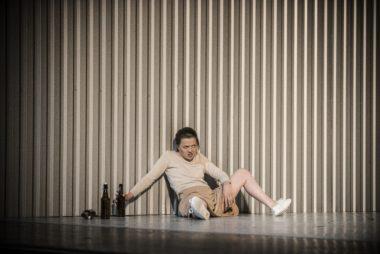 Kobieta na wpół siedząca na wpół leżąca z rozłożonymi nogami i butelką w ręce