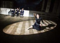 Aktorka tańcząca w świetle reflektora, na tle toje aktorów siedzących na krzesłach