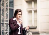 Aktor stojący na scenie z mikrofonem w ręce
