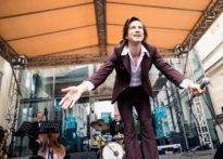 Aktor trzymający mikrofon w ręce kłaniający się widzom, w tle zespół muzyków