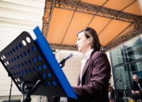 Aktor stojący przy mikrofonie,w tle muzyk ubrany w garnitur i muszkę
