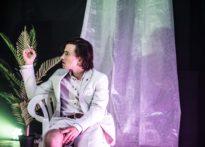 Aktor ubrany w krótkie spodnie i marynarkę na tle białej kotary i sztucznej palmy.