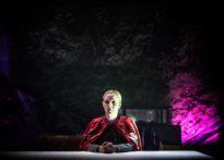 Kobieta siedząca przy stole ubrana w czerwoną pelerynę z białym krzyżem, w tle zdjęcie kamienia na fioletowej poświacie światła