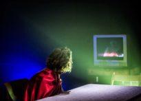Kobieta w siedząca przy stole, ubrana w czerwoną pelerynę oglądająca stojący w tle telewizor