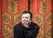 Aktor stojacy na scenie z wymalowaną na biało twarzą zakrywający ręką usta. W tle kurtyna aksamitna
