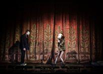 Aktor i aktorka stojący na scenie w tle kurtyna aksamitna. Aktorka ma na twarzy maskę klauna