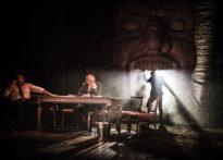 Dwóch aktorów siedzących przy stole, jeden z nich rozmawia przez telefon, w tle trzeci aktor wychodzący z jamy ustnej
