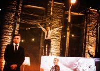Krzyczący aktor stojący na wysokości z rozłożonymi rękom, dalej aktorka i aktor stojący na dole na sceniea