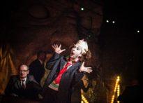 Aktor ze śmieszną miną i maską klauna nasuniętą na czoło, w tle siedzący lub chodzący aktorzy