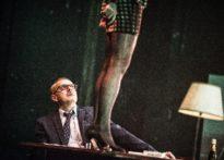 Na pierwszym planie aktorka stojąca na stole i jej odsłonięte nogi na drugim planie aktor siedzący przy stole i namiętnie wpatrujący się w aktorke