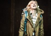 Krzycząca aktorka ubrana w zimową kurtkę z niebieskim plecakime której z prawego łuku brwiowego leci kres