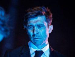 Aktor ze smutnym wyrazem twarzy ubrany w garnitur