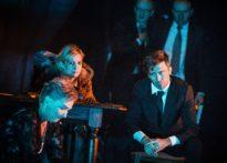 Na pierwszym planie aktorka siedząca na ziemi oraz kobieta i mężczyzna siedzący przy stole. Na drugim planie dwóch stojących mężczyzn w garnituracha