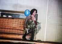 Aktora siedząca na wersalce z bukietem czerwonych róż w ręce i niebieskim balonem
