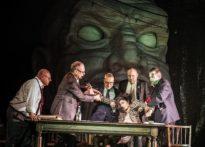 Aktora siedząca przy stole oraz czterech aktorów próbujących ją wyciągną zza stołu. Na zdjęciu również mężczyzna opierający się o stół o przypatrujący się. W tle wielka buzia