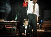 Aktor w garniturze siedzący na ziemi, za nim stoi mężczyzna trzymający kanister i oblewający go wodą