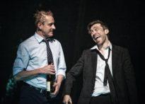 Uśmiechający się aktor z butelką wina w ręce oraz drugi aktor uśmiechający się