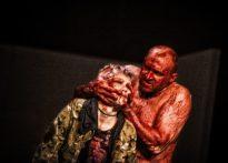 Mężczyzna bez koszuli umazany od pasa w górę krwią chwyta brudnymi rękoma aktorkę stojącą przed nim