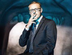 Aktor ubrany w garnitur palący papierosa na tel wielkiej jamy ustnej