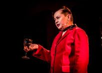 Aktorka ubrana w czerwoną marynarkę z kieliszkiem napoju w dłoni. Na zdjęciu Elżbieta Węgrzyn