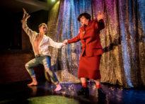 Para aktorów w czasie tańca- aktor w rozpiętej koszuli na bosaka, aktora przebrana w kostium oraz perukę na tle złotej kotary. Na zdjęciu Bartosz Dopytalski oraz Elżbieta Węgrzyn