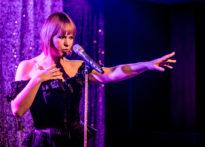 Aktorka stojąca przy mikrofonie w gorsecie na fioletowym tle. Na zdjęciu Kornelia Trawkowska