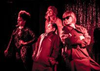 Cztery aktorki ubrane w prochowce oraz jedna aktorka ubrana w kombinezon koronkowy i czary skórzany płaszcz. Na zdjęciu Sylwia Achu, Barbara Prokopowicz, Kornelia Trawkowska oraz Elżbieta Węgrzyn