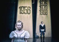 Na pierwszym planie aktorka w sukni, za nią aktor w białej koszuli z żabotem oraz surducie na tle repliki Poznański Krzyży