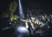 Na pierwszym planie aktor leżący na ziemi w samej bieliźnie a nad nim pochylająca sie kobieta, na drugim planie aktorzy oraz publiczność
