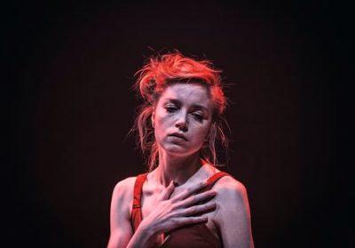 Aktorka ubrana w czerwony top na ramiączkach.