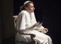 Aktor siedzący na krześle ubrany w strój papieski z gołymi stopami.