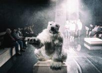 Na pierwszym planie postać przebrana za polarnego misia, na drugim publiczność oraz aktorzy.
