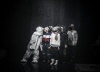 Aktorzy na tle Poznański Krzyży, koło nich postać przebrana w strój misia polarnego. Zdjęcie zbiorowe