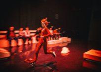 Kobieta biegnąca przez scenę, w oddali rozmazane postacie widzów