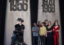 aktorka ubrana na czarno z woalką na twarzy stojąca przy pulpicie do nut, za nią pozostali aktorzy na tle Poznańskich Krzyży