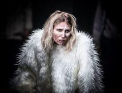 Aktorka ubrana w białe futerko z białym makijażem na twarzy