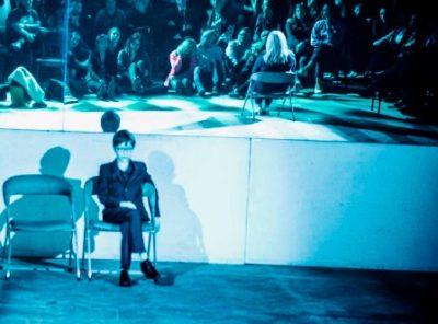 młody chłopiec siedzący na krześle z założoną nogą na nogę. W tle lustro w którym odbija sie publiczność i pozostali aktorzy.