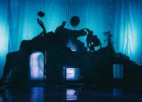 Zarysy postaci aktorów na scenografii w niebieskim świetle