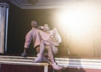 Dwóch mężczyzn splątanych ze sobą stojących na elemencie loży teatralnej