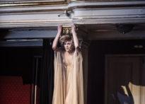 Aktorka ubrana w przezroczystą sukienkę stojąca na elemencie loży teatralnej